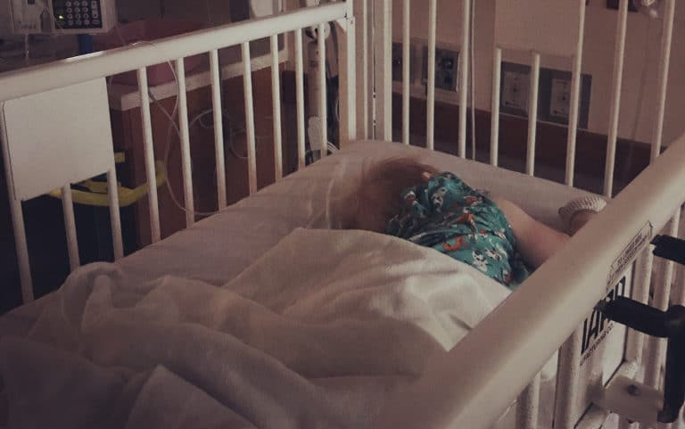 Child lying in a hospital crib surrounded by medical equipment