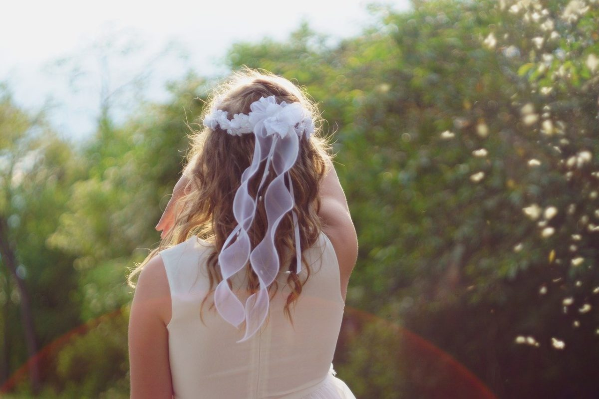 Girl in first communion dress, back turned to camera, wearing a flower tiara with trailing ribbons