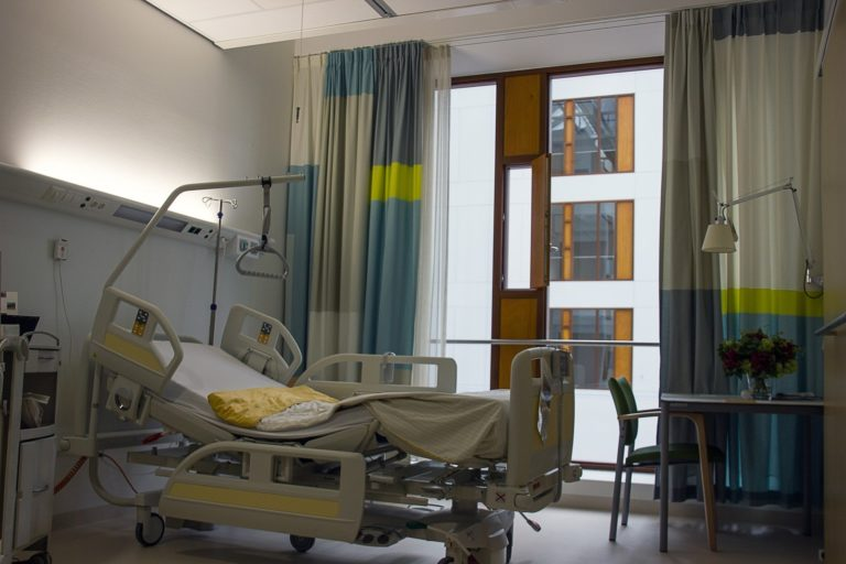 Empty hospital bed in front of an open window