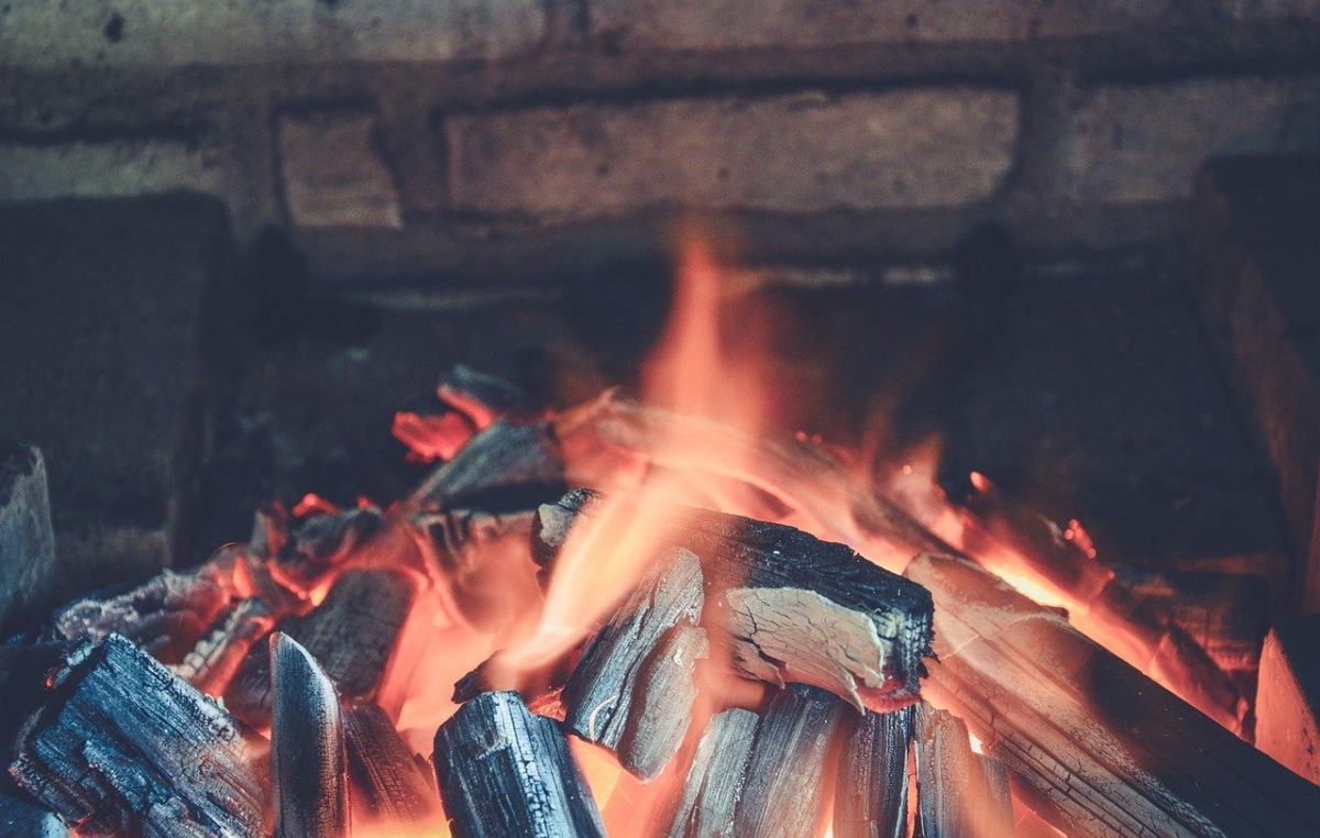 Flames and a pile of coals in a brick fireplace