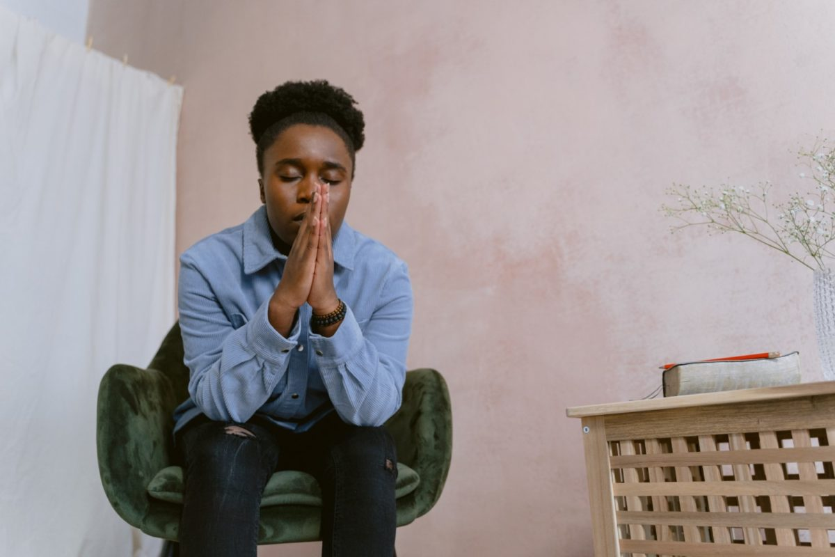 An Afro-Haired Woman Sitting on a Chair while Praying