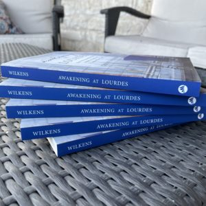 Five copies of Awakening at Lourdes, fanned out in a stack on a wicker table, spines facing out.