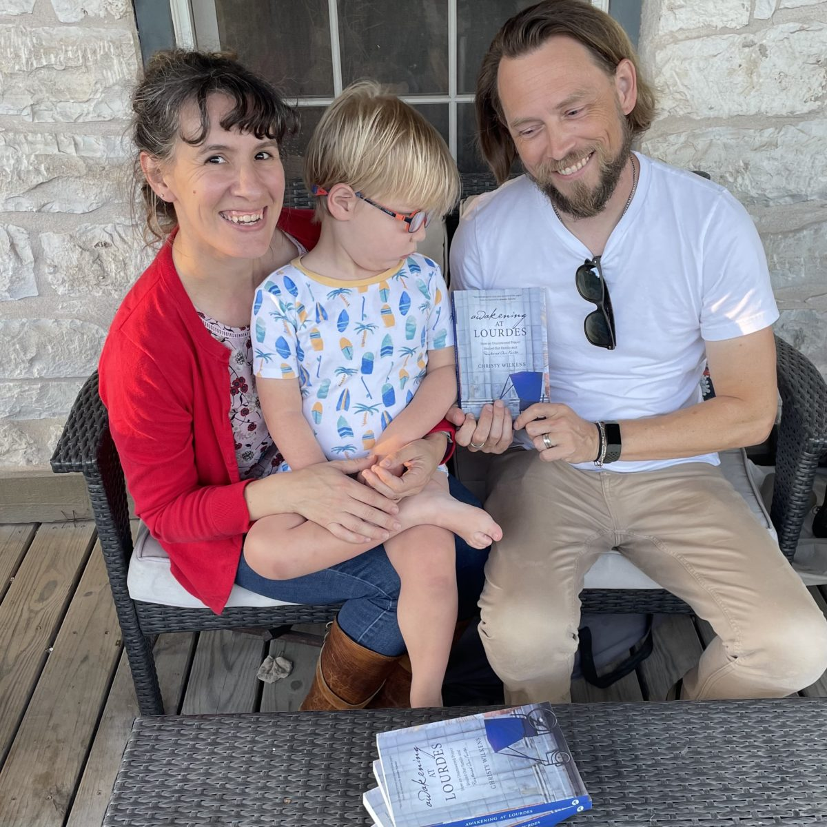 Christy, Todd, and Oscar sit on a wicker bench. Todd is holding a copy of Awakening at Lourdes. On her lap, Christy holds Oscar, who is looking t